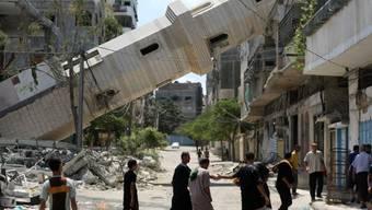 Palästinenser vor zerstörtem Minarett in Gaza-Stadt