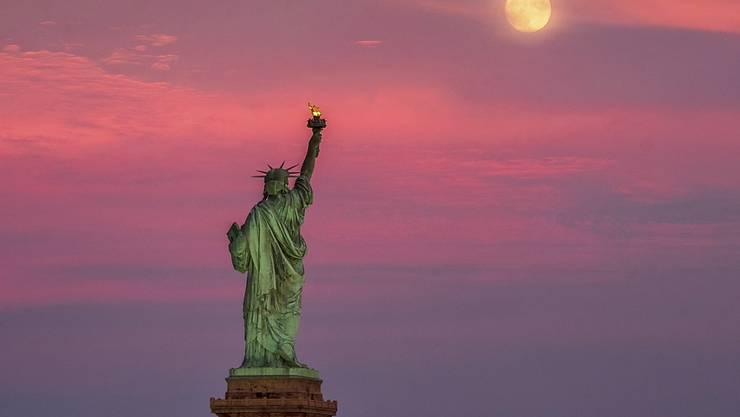 ARCHIV - Der Vollmond erhebt sich bei Sonnenuntergang hinter der Freiheitsstatue in New York. In der Millionenmetropole hat es vorläufigen Daten zufolge erstmals seit dem Ausbruch einen Tag ohne bestätigten oder wahrscheinlichen Todesfall nach einer Infektion mit dem Virus gegeben. Foto: J. David Ake/AP/dpa