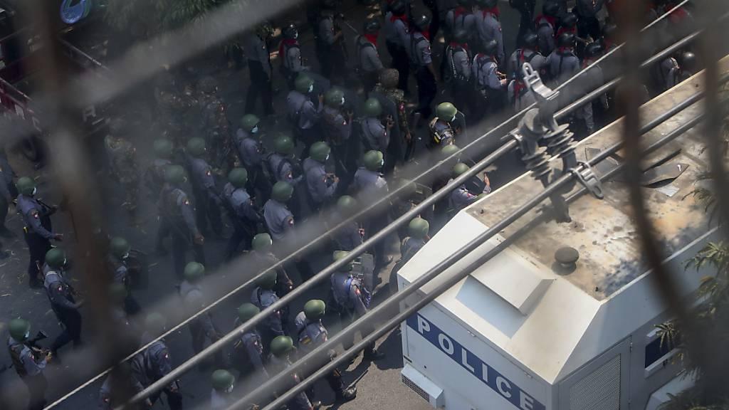 Polizisten und Soldaten, die mit Gewehren und Steinschleudern bewaffnet sind, nähern sich den Demonstranten in Mandalay bei einem Protest gegen den Militärputsch. Foto: Str/AP/dpa