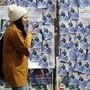 Eine Iranerin läuft an den Wahlplakaten vorbei.