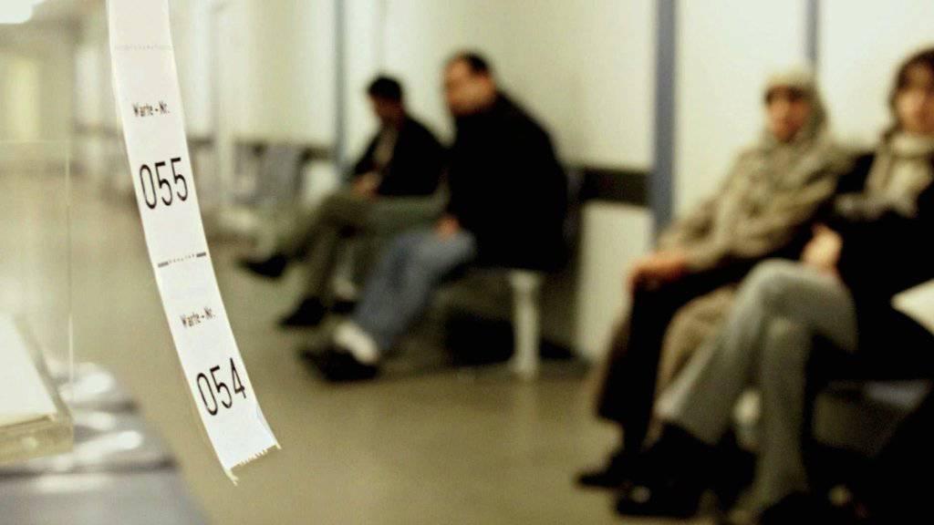 Menschen warten auf einem Arbeitsamt. (Symbolbild)
