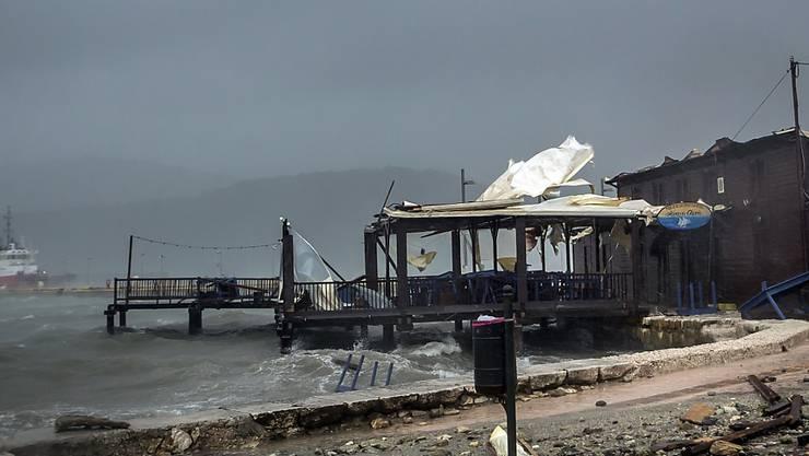 Wellen brechen im Hafen von Argostoli in einer Taverne ein. Der schwere Herbststurm «Ianos» hat sich langsam entlang der Küste der griechischen Halbinsel Peloponnes bewegt - und dabei erhebliche Schäden angerichtet. Foto: Nikiforos Stamenis/AP/dpa