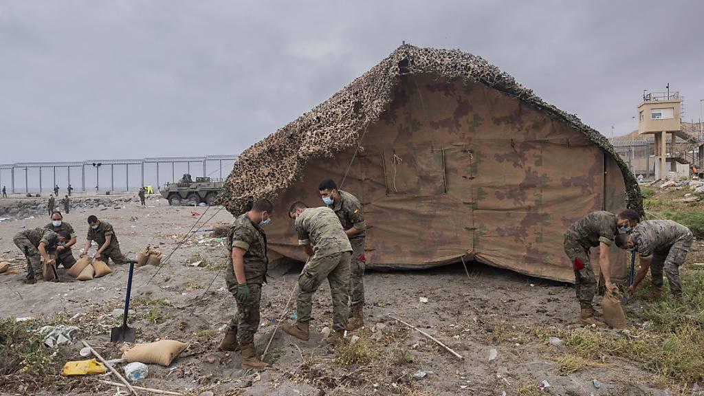 Soldaten der spanischen Armee errichten ein Zelt in der spanischen Enklave Ceuta, direkt an der Grenze zwischen Marokko und Spanien. Foto: Bernat Armangue/AP/dpa