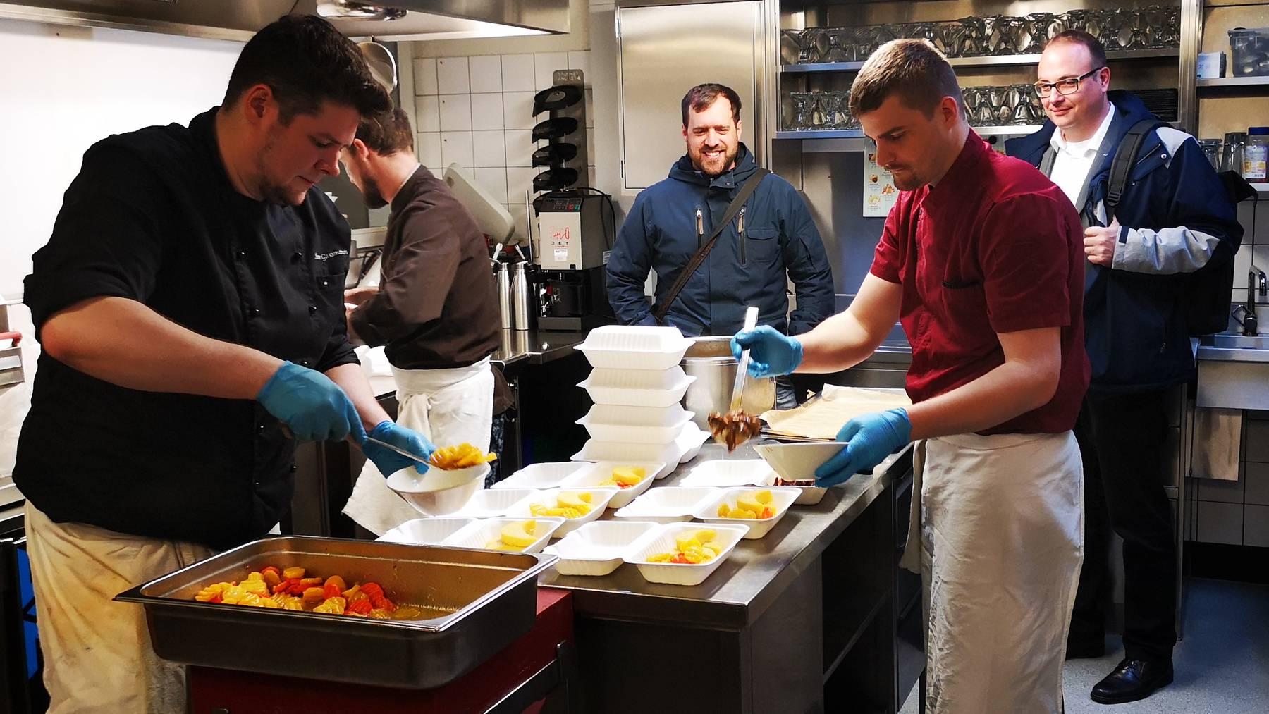 In der «Felmis»-Küche sind die Fachleute an der Arbeit; beobachtet vom katholischen Pfarrer Benedikt Wey (hinten rechts) und dem reformierten Jonas Oesch (links).
