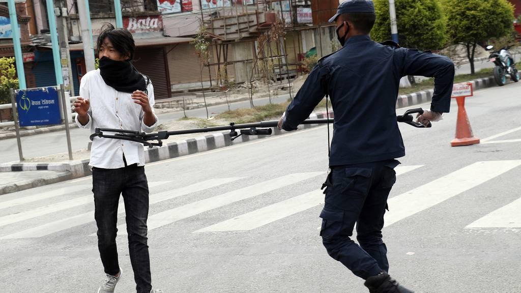 Social Distancing: Nepals Polizisten nehmen Leute mit Klammern fest