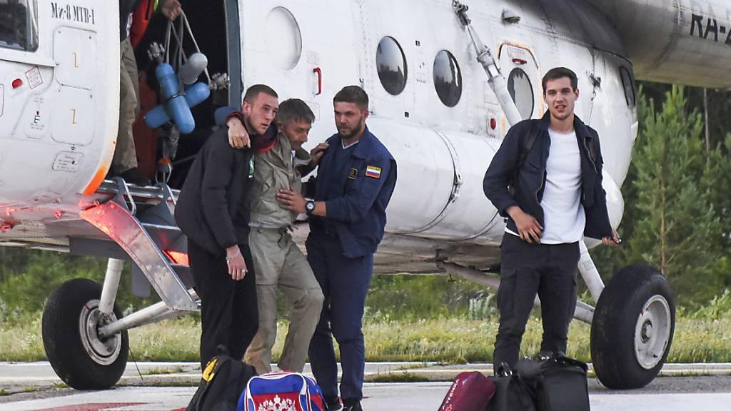 Der Pilot Anatolij Prytkow (M) wird nach der Notlandung eines kleineren Passagierflugzeugs mit 18 Menschen an Bord von seinen Kollegen gestützt. Laut Angaben des Ermittlungskomitees könnte ein Ausfall beider Triebwerke die Ursache der Bruchlandung im russischen Tomsk gewesen sein. Foto: Taisya Vorontsova/RIA Tomsk/AP/dpa