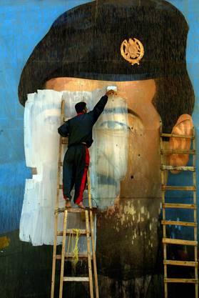 Das Symbol des Umsturzes: Carolyn Cole dokumentiert wie ein von Schüssen durchlöchertes Wandbild von Saddam Hussein 2003 kurz nach dem Einmarsch der US-Truppen in Bagdad übermalt wird.