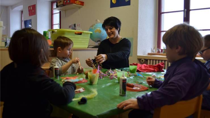 Krippenleiterin Monica Moser hilft den Kindern beim Basteln mit bunten Materialien.