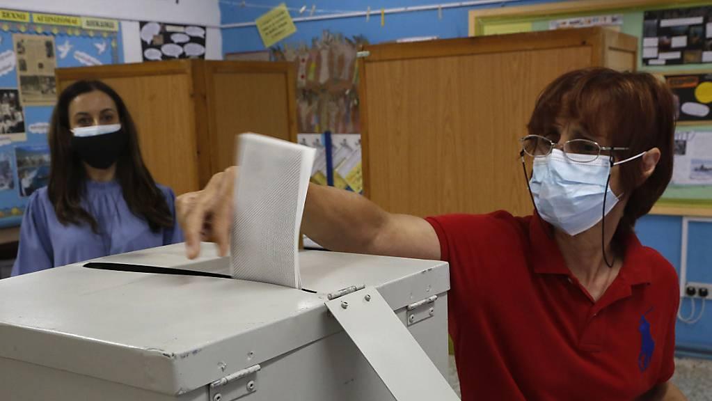 Eine Frau mit Mund-Nasen-Schutz gibt ihre Stimme in einem Wahllokal während der Parlamentswahlen ab.