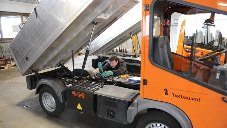 Fahrzeugelektriker Martin Waldmeier kontrolliert den Batteriestand bei einem Fahrzeug der Stadtreinigung.