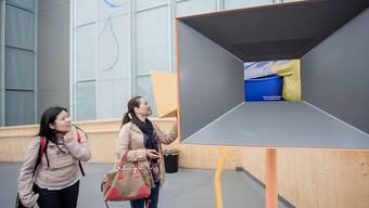 Zwei Expo-Besucherinnen vor einem Bildschirm ausserhalb des Schweizer Pavillons