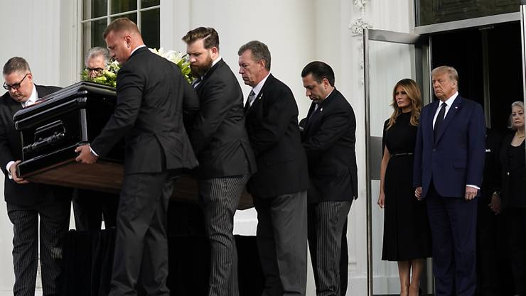 US-Präsident Donald Trump und First Lady Melania Trump stehen nebeneinander, während der Sarg von Robert Trump nach einer Gedenkfeier im Weißen Haus in einen Leichenwagen geladen wird. Foto: Evan Vucci/AP/dpa