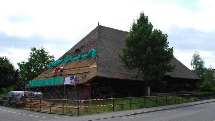 Das Strohhaus-Dach wird gepflegt.