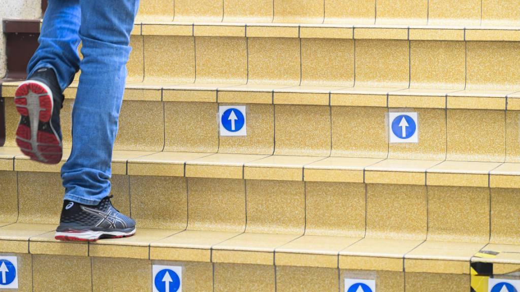 Ein Schüler geht während der Wiedereröffnung einer Sekundärschule in Brüssel eine Treppe mit Markierungen hinauf. Foto: Laurie Dieffembacq/BELGA/dpa