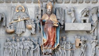 Sankt Nikolaus hält am Portal der Kathedrale von Freiburg (i. Ü.) drei Goldkugeln bereit.