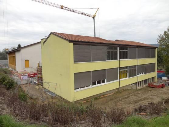 Im Vordergrund das bestehend Münchwiler Schulhaus, hinten die Turnhalle