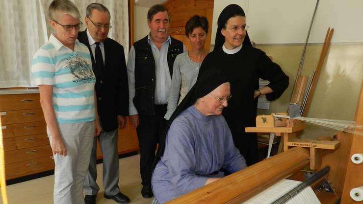 Maria Wüest, Roman Brüschweiler, Martin Egli, Priska Schmid und die Priorin Irene Gassmann (von links) schauen Schwester Martina Meyer bei den Vorbereitungen am Webstuhl über die Schultern.