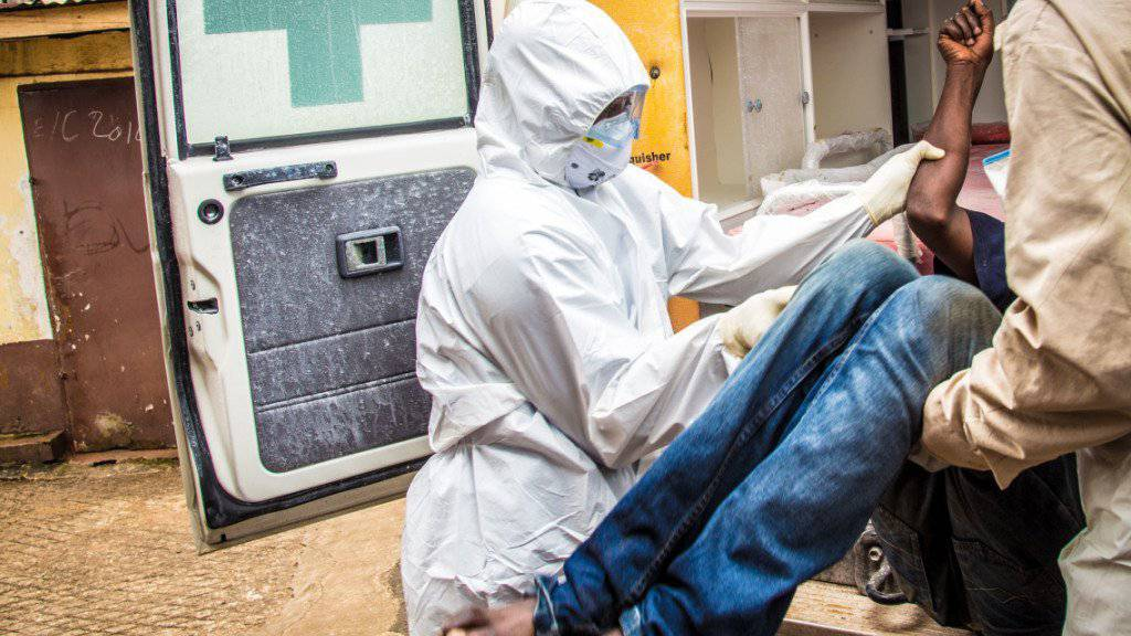 Mitarbeiter der Gesundheitsdienste tragen zum Höhepunkt der Ebola-Epidemie einen Ebola-Kranken in eine Ambulanz. In Sierra Leone ist erneut ein Ebola-Fall aufgetaucht. (Archiv)