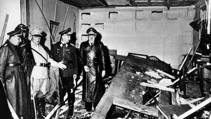 NS-Reichsleiter Martin Bormann (links) und Reichsmarschall Hermann Göring (helle Uniform) begutachten die Zerstörung in Hitlers Besprechungsbaracke.