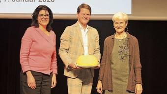Barbara Horlacher (links) und Heidi Ammon überreichen dem Referenten Peter Staub einen Kuchen mitsamt Glasteller.