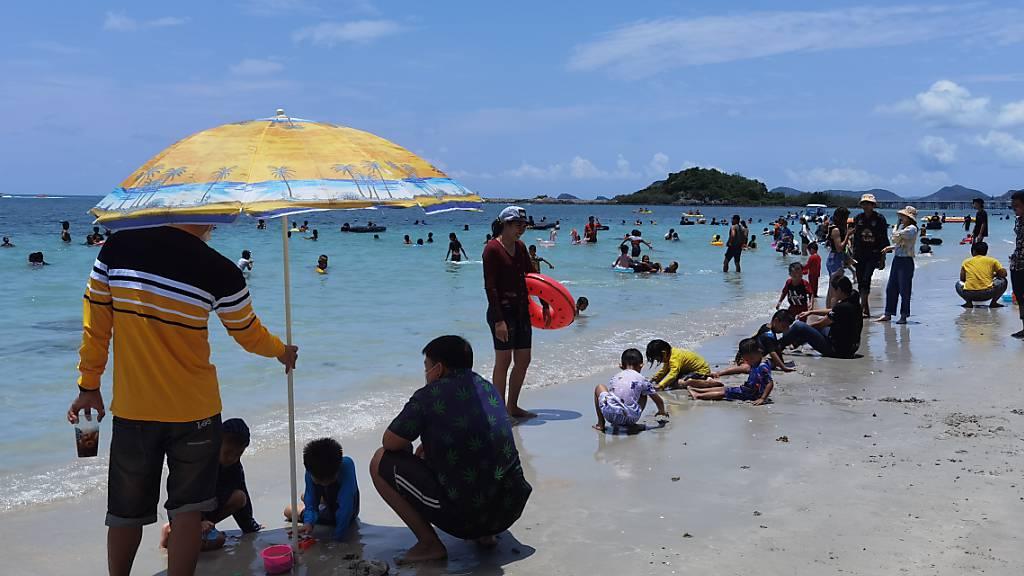 ARCHIV - Einheimische und Touristen genießen die Zeit am Strand von Chonburi in Thailand. (Archivbild) Foto: Penny Yi Wang/AP/dpa