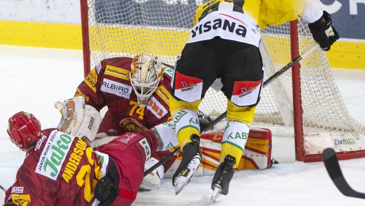 Der Langnauer Torhüter Ivars Punnenovs und Verteidiger Toms Andersons wehren sich gegen SCB-Stürmer Simon Moser (rechts)