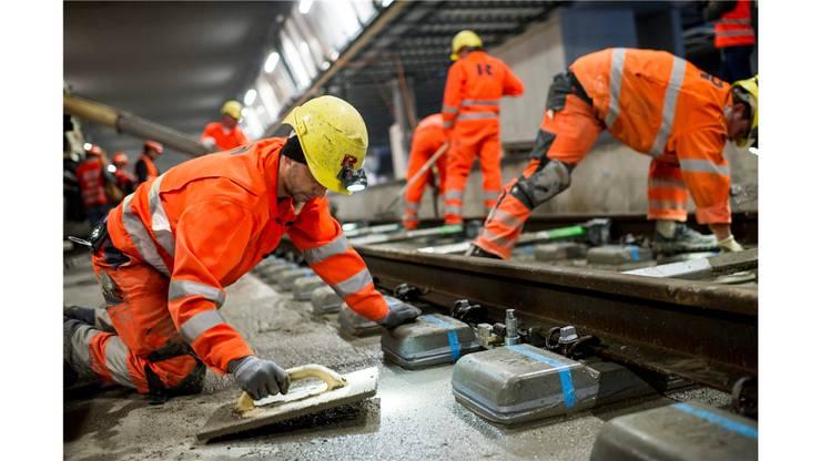 Bauarbeiter betonieren die Gleise ein.