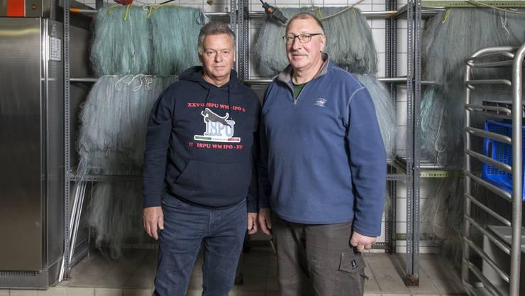 """Vereinspräsident Erwin Hert (links) und Martin """"Tinu"""" Fischer in der Brutanstalt in Meisterschanden. Hinter ihnen Hängen Fischernetze. Diese kosten pro Stück um die 1000 Franken."""