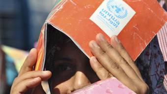 Ein palästinensischer Lehrer bedeckt seinen Kopf während einer Demonstration mit einem Schulheft (Archiv)
