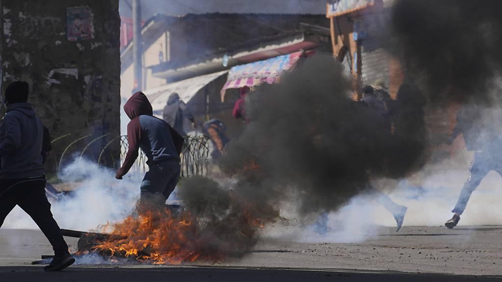Kokabauern fliehen vor Tränengas, das von der Polizei in La Paz abgefeuert wurde. Die regierungsfeindlichen Kokabauern versuchten, den Kokamarkt mit Gewalt zu übernehmen, nachdem sie die Kontrolle verloren hatten, als eine andere Gruppe von Kokabauern einen neuen Anführer wählte. Foto: Juan Karita/AP/dpa