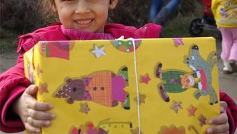Ein Mädchen freut sich über ihr Weihnachtspäckli aus der Schweiz.