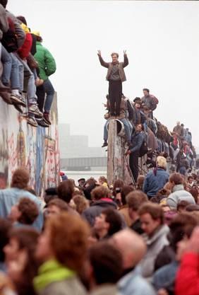 Ein Berliner feiert das Ende der Berliner Mauer.