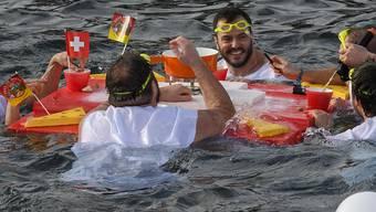 Diese Teilnehmer haben sich für das Weihnachtsschwimmen im 6,1 Grad kalten Genfersee ein erwärmendes Motto ausgedacht.