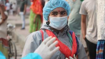 In Schutzkleidung spricht Moonmoon, ein Mitglied der Transgender-Gemeinschaft, mit Bedürftigen, die am Straßenrand des Stadtviertels Badda nach Brauchbarem suchen. Foto: Nazrul Islam/dpa