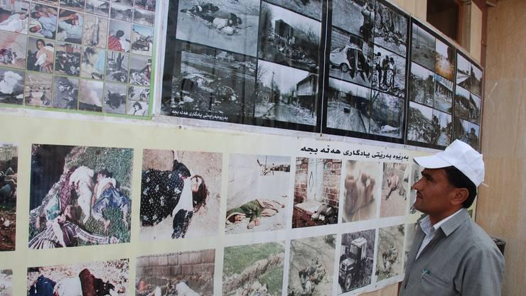 Ein Kurde betrachtet die Bilder des Massakers.