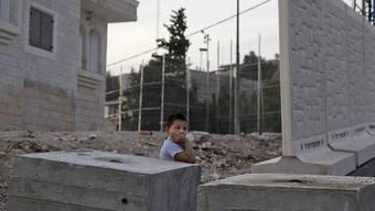 Ein Palästinenser-Junge steht vor den Mauer-Elementen, die von Israel zwischen Dschabal Mukaber und Armon Hanaziv errichtet werden.