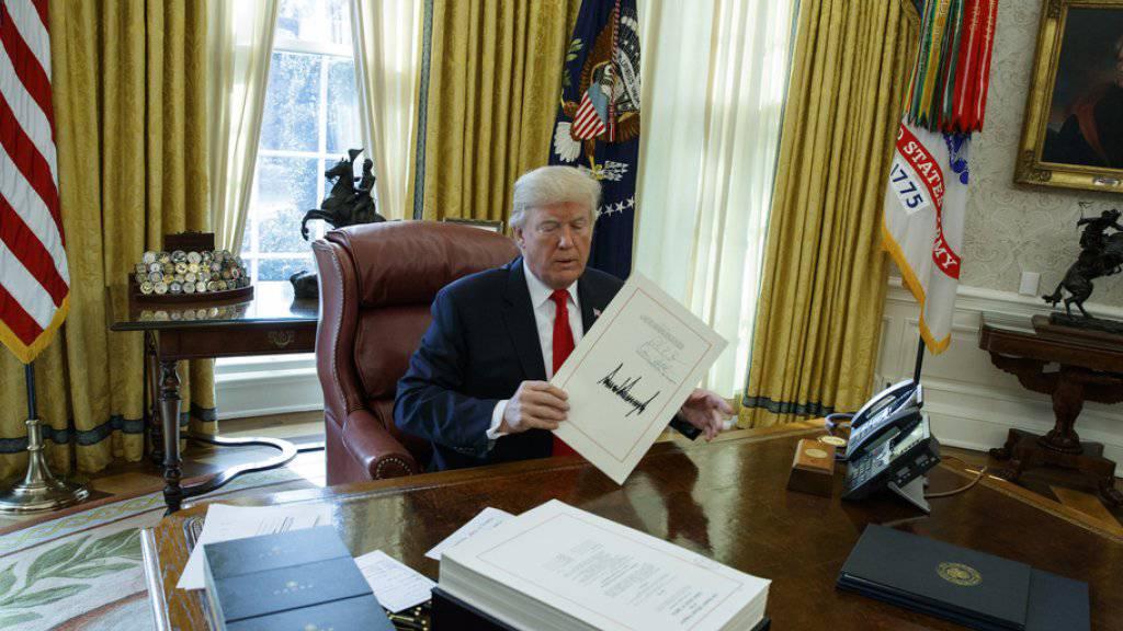 Donald Trump hält am Freitag im Oval Office die von ihm unterzeichnete tax bill hoch.