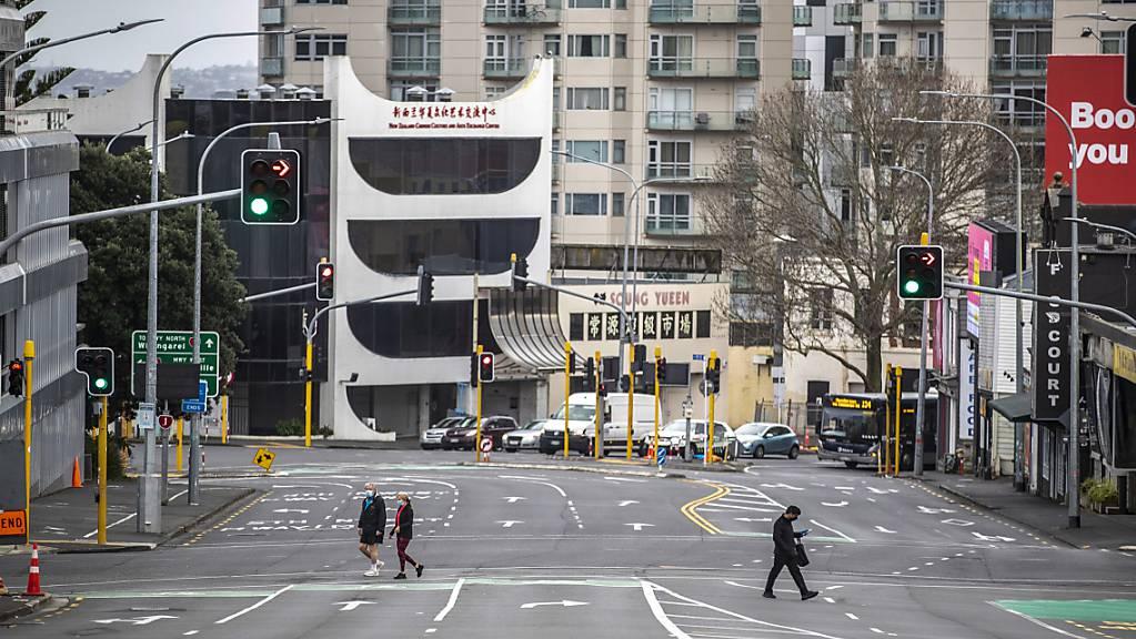 Menschen überqueren im zentralen Geschäftsviertel fast leere Straßen. Aufgrund von sinkenden Corona-Zahlen wird nach einem Monat des strengen Lockdowns in der neuseeländischen Millionenmetropole Auckland gelockert. Das teilte die Regierung am Montag mit. Foto: Michael Craig/New Zealand Herald/dpa