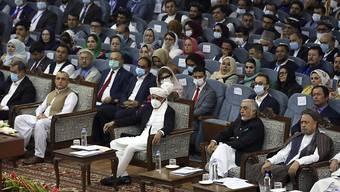 Aschraf Ghani (M), Präsident von Afghanistan, trägt eine FFP-Maske bei der Loja Dschirga, der großen Ratsversammlung. Ghani hatte die Loja Dschirga einberufen, um über das Schicksal von 400 inhaftierten Taliban zu entscheiden, denen teils schwerste Verbrechen vorgeworfen werden. Foto: Rahmat Gul/AP/dpa