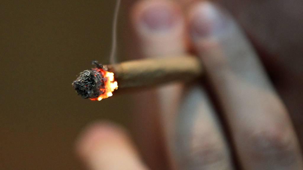 ARCHIV - ILLUSTRATION - Ein Mann raucht in einem Coffee Shop einen Joint mit Marihuana. Foto: picture alliance / Oliver Berg/dpa
