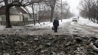 Ein Mann steht im Gebiet von Donezk an einer zerstörten Strasse