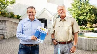 Gemeindepräsident André Bender und Autor Peter Naef präsentieren die neue Chronik auf dem Dorfplatz.
