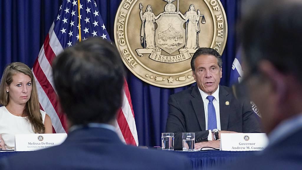 Die Sekretärin des Gouverneurs Melissa DeRosa, (l), hört zu, wie der New Yorker Gouverneur Andrew Cuomo während einer Pressekonferenz zu Reportern spricht.