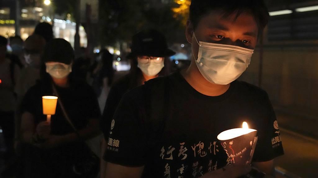 Menschen gehen mit Kerzen in den Händen vor dem Victoria Park entlang. Bereits in den vergangenen Jahren hatten sich dort etliche Menschen zum Jahrestag der blutigen Niederschlagung der Demokratiebewegung am 4. Juni 1989 in Peking versammelt. Foto: Kin Cheung/AP/dpa