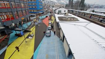Blick auf den mit farbigen Rauten bemalten länglichen Bahnhofplatz von Horgen.
