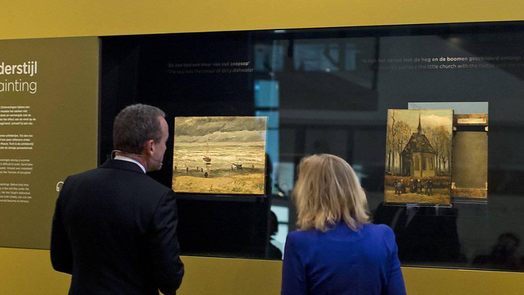"""Axel Rueger, der Direktor des Van Gogh Museums, und Bildungsministerin Jet Bussemaker vor den beiden Van Goghs, die 14 Jahre, nach dem sie geraubt wurden, wieder """"zu Hause"""" sind."""