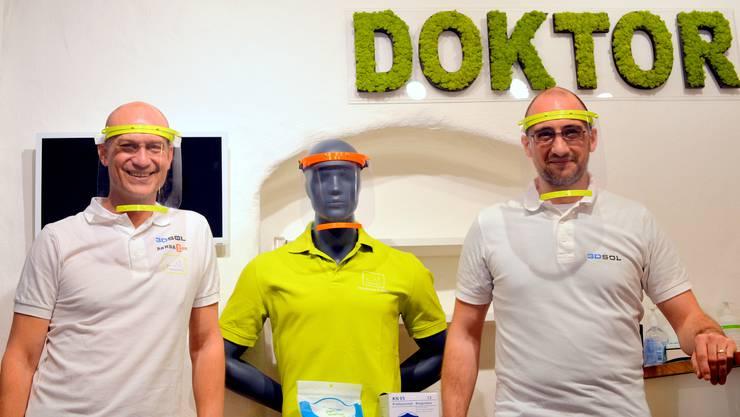 Markus Arni und Michael Wirz demonstrieren ihren Gesichtsschild aus dem 3D-Drucker.
