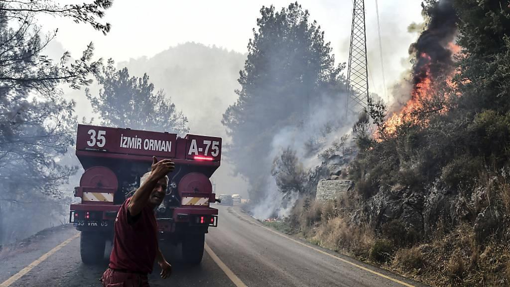 Ein Feuerwehrmann gestikuliert hinter einem Löschzug während am rechten Hang ein Feuer zu sehen ist. Foto: Ismail Coskun/IHA/dpa