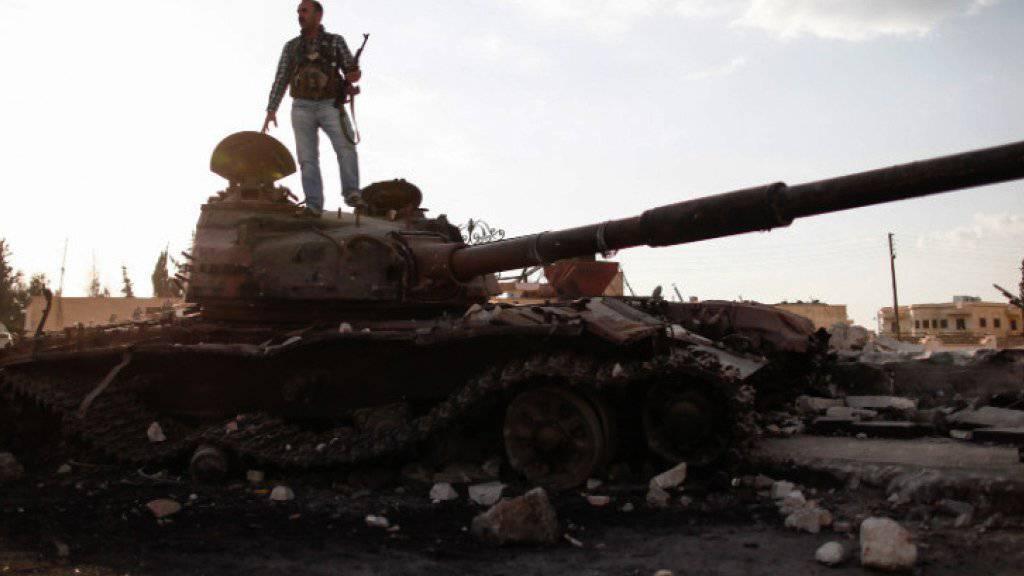 Die Aufnahme aus dem Jahr 2013 zeigt einen Kämpfer der Freien Syrischen Armee, der auf einem beschädigten Panzer in Sabadani steht. Die Kämpfe um die strategisch wichtige Stadt nahe Damaskus sind am Samstag wieder aufgeflammt (Archiv)