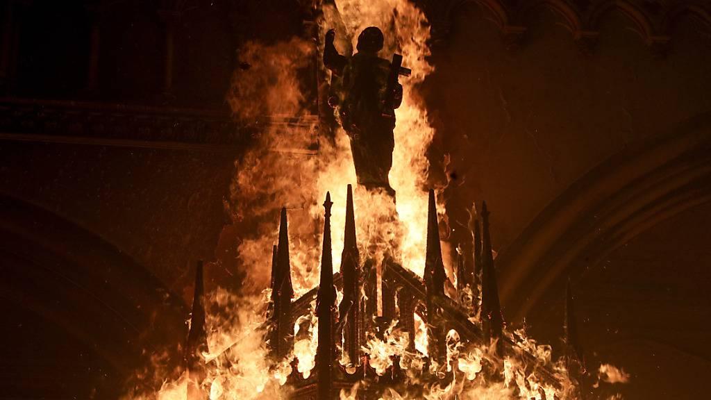 Eine Heiligenfigur in der brennenden Kirche San Francisco de Borja in Chiles Hauptstadt Santiago. Foto: Esteban Felix/AP/dpa